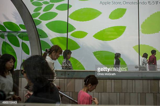 People enter the metro station in front of the construction wall of the new Apple store at Omotesando on June 4 2014 in Tokyo Japan The new store...