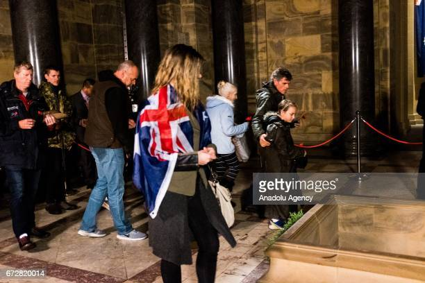 People enter the shrine as they place poppies in respect of the fallen during the dawn service of the ANZAC day commemoration at the Shrine of...