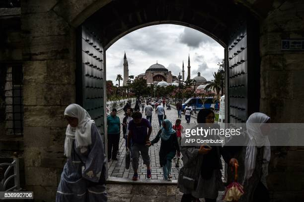 TOPSHOT People enter to Sultanahmet mosque on August 22 2017 near the Hagia Sophia during a rainy day in Istanbul / AFP PHOTO / OZAN KOSE