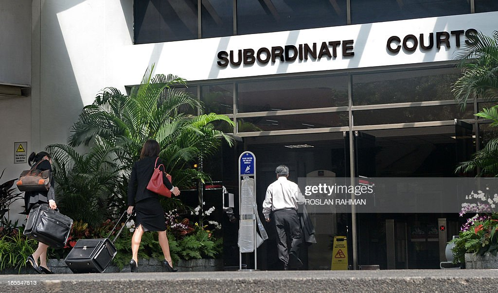 People enter to the Subordinate Courts in Singapore on April 5, 2013. Three Lebanese soccer referees were charged on April 4 for receiving sexual bribes in exchange for fixing a match in Singapore, the government's anti-corruption bureau said.