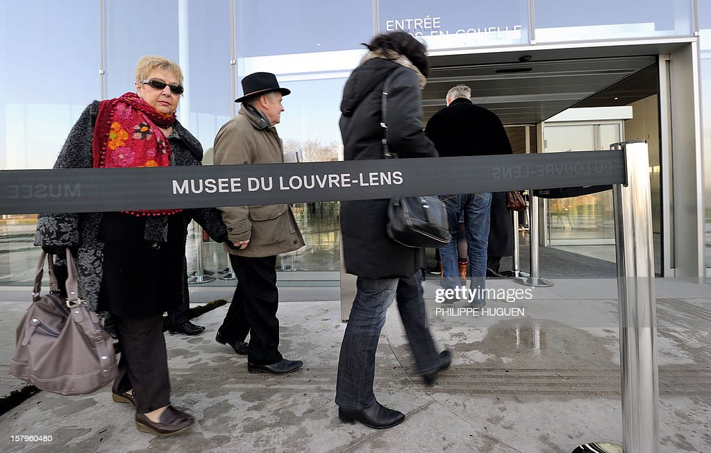 People enters the Louvre-Lens museum on December 8, 2012 in Lens, northern France. The Louvre museum opened a new satellite branch among the slag heaps of a former mining town on Dcember 4, 2012 in a bid to bring high culture and visitors to one of France's poorest areas. AFP PHOTO PHILIPPE HUGUEN
