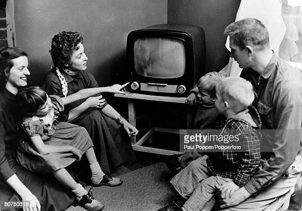 People Entertainment Domestic appliances USA pic circa 1954 A family gather around the television in an American home