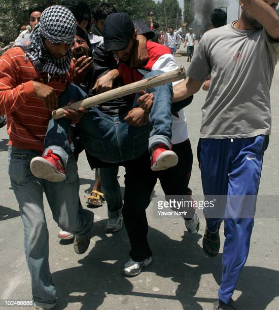 People evacuate a wounded protester after Indian police fired bullets indiscriminately on them on the street during a protest of the deaths of three...