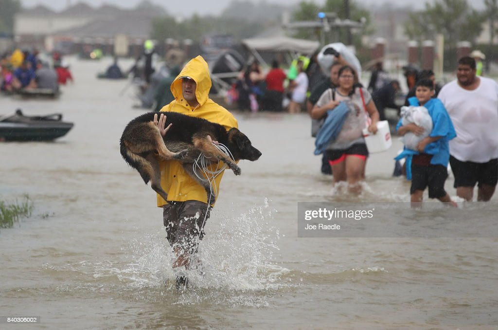 People evacuate their homes after the area was inundated with flooding from Hurricane Harvey on August 28, 2017 in Houston, Texas. Harvey, which made landfall north of Corpus Christi late Friday evening, is expected to dump upwards to 40 inches of rain in Texas over the next couple of days.