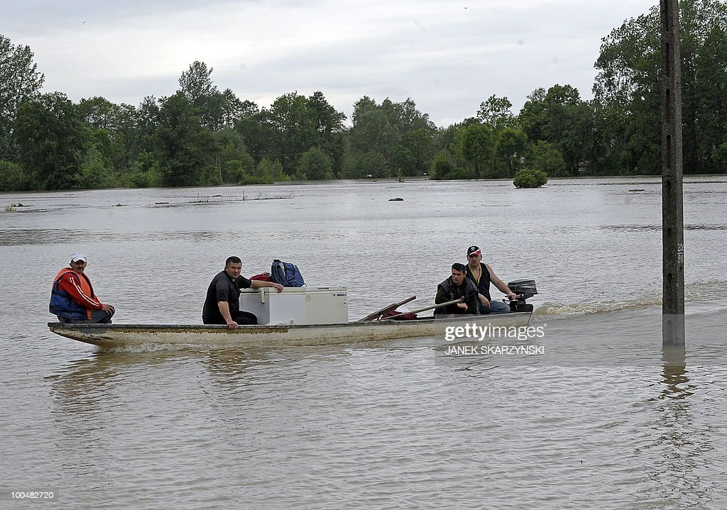 People evacuate their staff from a flooded farm in Juliszew village in central Poland at Wisla river on May 24, 2010 Flash floods caused by days heavy rainfall have hit parts of central Europe, killing at least 14 people, disrupting power supplies and forcing thousands of people from their homes.