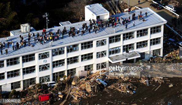 People evacuate to the roof of an elementary school as the sudden tsunami caution is announced after an 90 magnitude strong earthquake struck on...