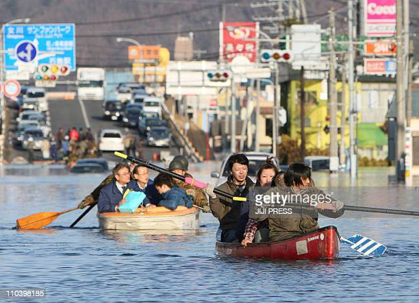 People evacuate with small boats down a road flooded by the tsunami waves in the city of Ishinomaki in Miyagi prefecture on March 12 2011 a day after...