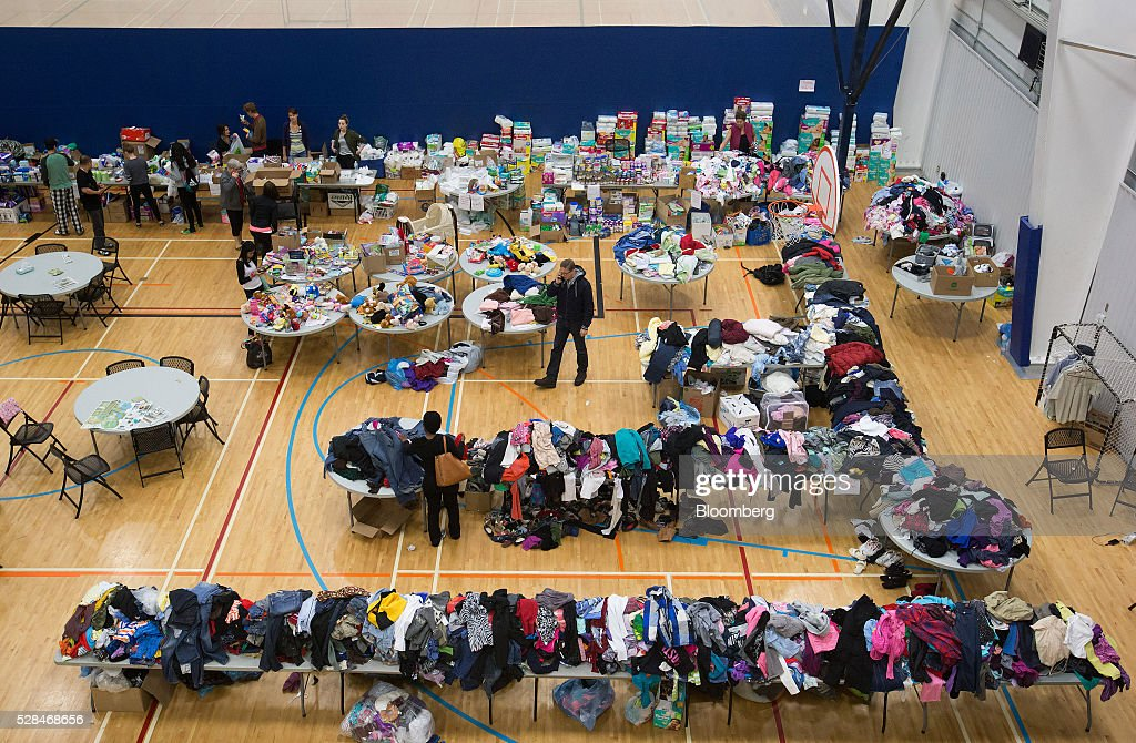 People evacuated due to wildfires in the Fort McMurray area browse through clothing donations and other supplies at a community centre in Lac La Biche, Alberta, Canada, on Thursday, May 5, 2016. A fire fueled by shifting winds that forced more than 80,000 people to flee their homes and threatened the business district of oil-sands hub Fort McMurray, Canada, raged out of control Wednesday after consuming 80 square kilometers (30 square miles) of land and damaging 1,600 buildings. Photographer: Darryl Dyck/Bloomberg via Getty Images