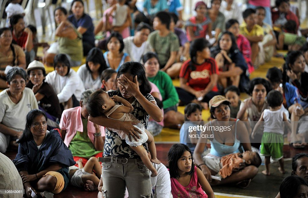 People evacuated from the breakwater of Manila Bay queue up to recieve food handouts from the local government at a converted basketball court in Manila on October 19, 2010. The strongest typhoon to hit the Philippines in years killed at least 10 people as it generated waves as big as houses and destroyed swathes of vital rice crops, authorities said. Many areas in the north of the Philippines' main island of Luzon remained without power and communications facilities, a day after Super Typhoon Megi ripped over the region with wind gusts of 260 km per hour (161 mph).