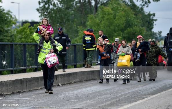 People evacuated from their flooded houses cross a bridge in the town of Obrenovac 40 kilometers west of Belgrade on May 17 2014 Deadly floods across...