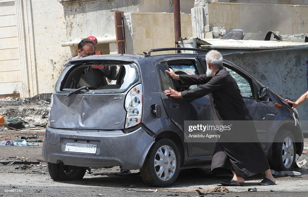 People examine a damaged car in front of the Suayb mosque after a car bomb attack during Friday prayer in Idlib, Syria on May 27, 2016.