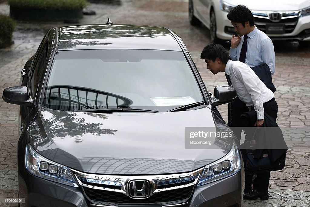 People examine a Honda Motor Co. Accord hybrid sedan displayed at its unveiling in Tokyo, Japan, on Thursday, June 20, 2013. Honda, Japan's third-largest carmaker, unveiled a hybrid sedan at a 20 percent higher price than Toyota Motor Corp.'s gasoline-electric Camry, betting drivers will pay extra for fuel economy. Photographer: Kiyoshi Ota/Bloomberg via Getty Images