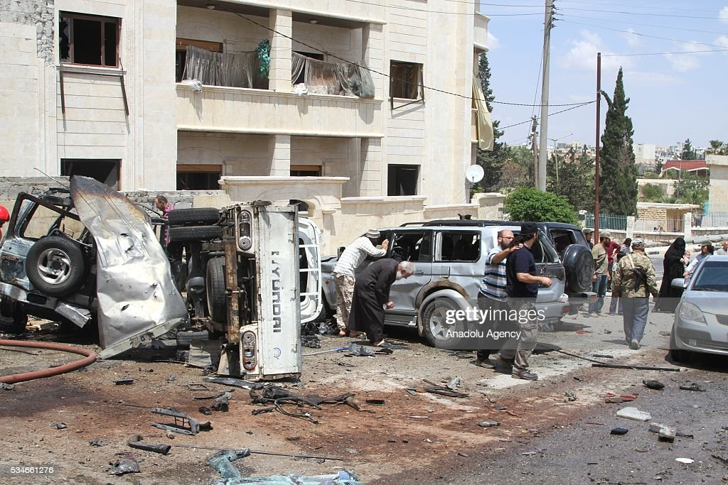 People examine damaged cars in front of the Suayb mosque after a car bomb attack during Friday prayer in Idlib, Syria on May 27, 2016.