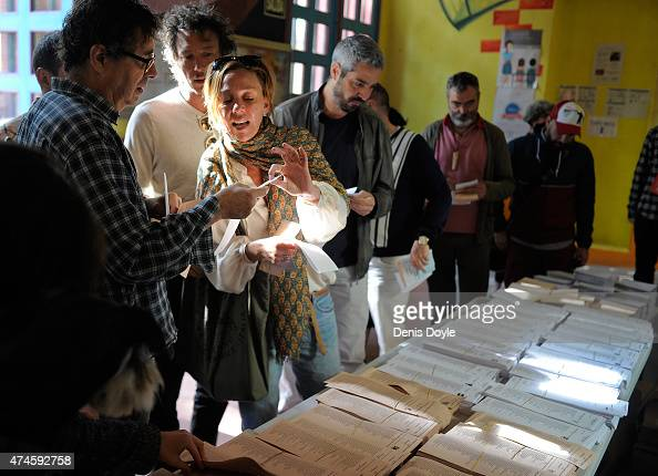 People examine the list of candidates before voting at a polling station in the Malasana district of Madrid on May 24 2015 in Madrid Spain Spaniards...