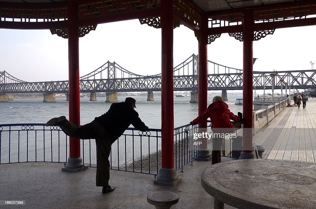 People exercise before the Sino-Korean Friendship Bridge in the Chinese border city of Dandong, northeastern Liaoning province on April 10, 2013. The biggest border crossing between North Korea and China has been closed to tourist groups, a Chinese official said on April 10 as nuclear tensions mounted, but business travel was still allowed. AFP PHOTO / WANG ZHAO