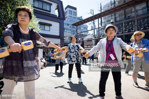 People exercise with wooden dumbbells during an event marking Respect for the Aged Day at a temple in the Sugamo shopping district on September 18...