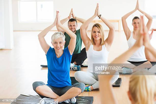 People exercise yoga at health club