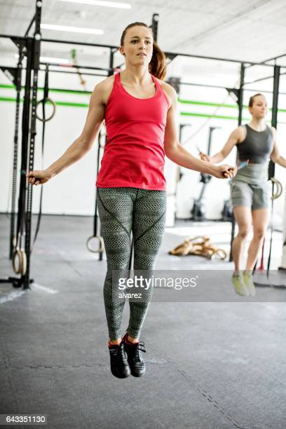 People exercising with jumping ropes at gym