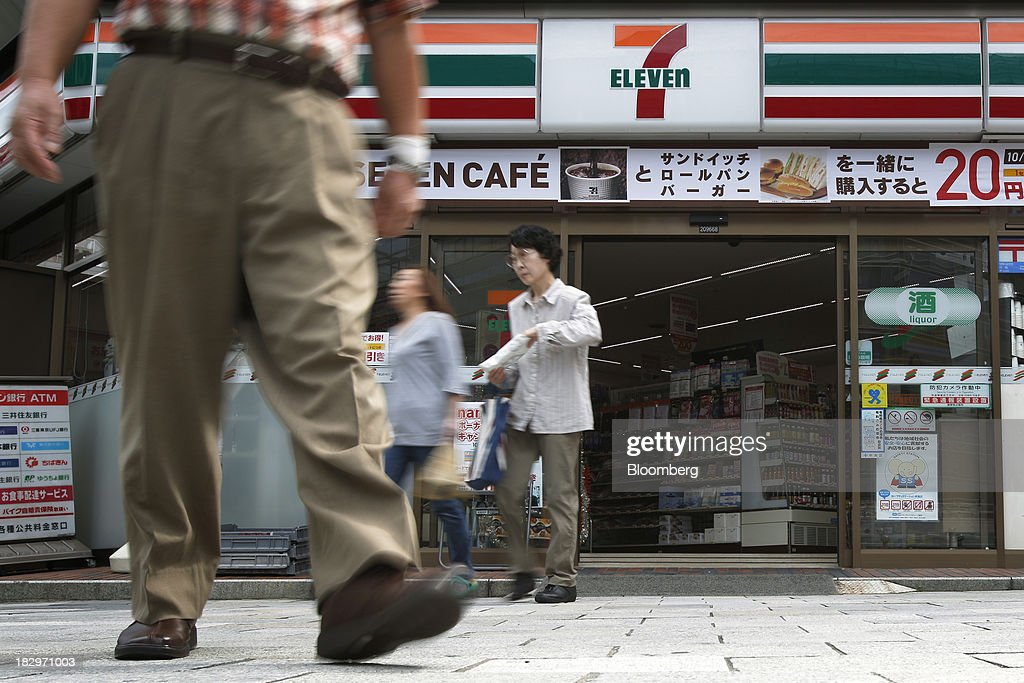 People exit a 7-Eleven convenience store, operated by Seven & I Holdings Co., in Tokyo, Japan, on Thursday, Oct. 3, 2013. Seven & I reported a 25 percent rise in first-half net income, in line with analysts' estimates. Photographer: Kiyoshi Ota/Bloomberg via Getty Images