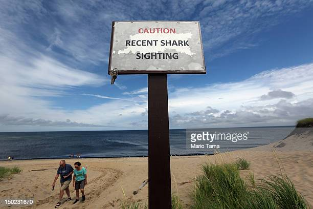 People exit the beach near a 'Recent Shark Sighting' sign near where a colony of several hundred seals often rest on a sandbar at High Head Beach on...
