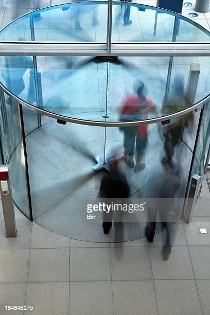 People Exiting Building Through Revolving Door