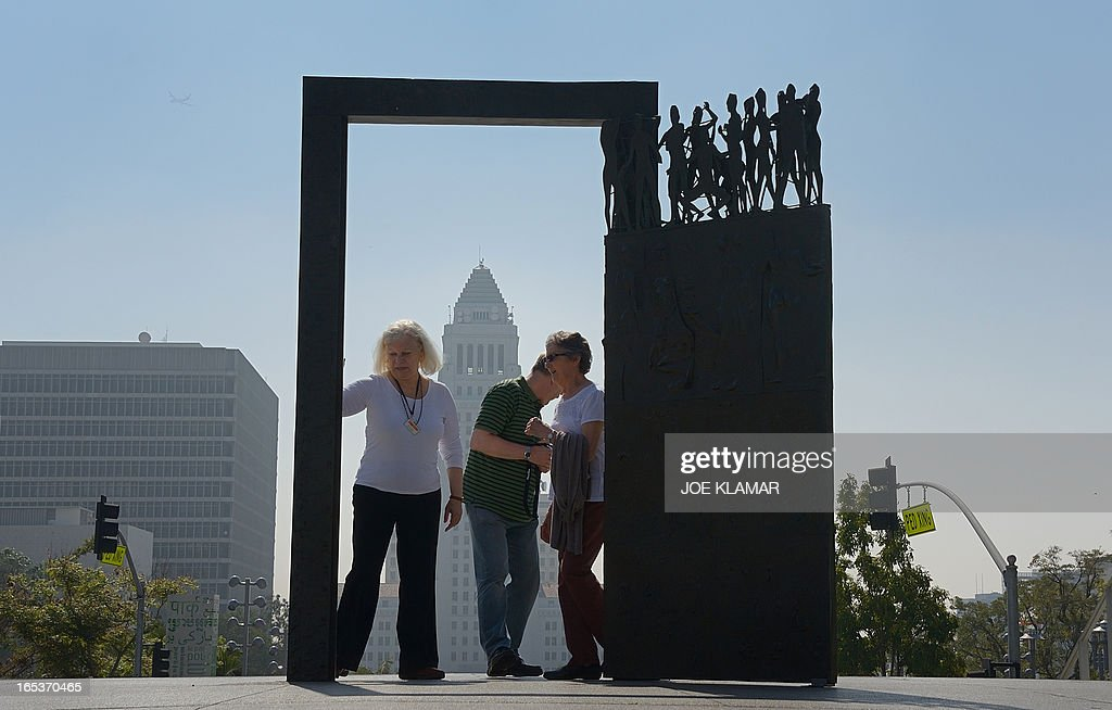 People explore 'Dance Door' in Los Angeles, California on April 03, 2013. 'Dance Door,' by artist Robert Graham, is installed in front of Los Angeles Music Center and it was gift of Frederic R Weisman. The Los Angeles City Hall is in the background.