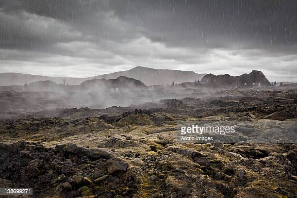 People exploring steaming lava fields in the rain