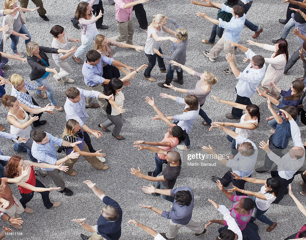 People extending arms to each other in crowd : Stock Photo