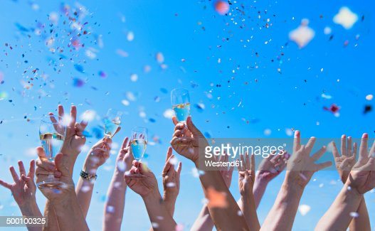 People exulting, Arms raised with champagne glasses, confetti