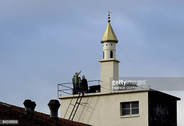 People face a minaret build on the top of a chimney on December 10 2009 in BussignypresLausanne western of Swistzerland to protest agaisnt a recent...