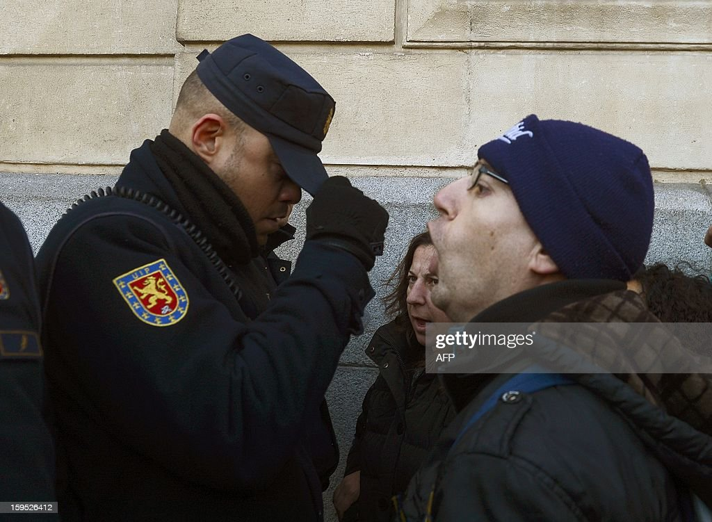 People facing foreclosure (R) protest in front of policemen securing a building where the Spain Investors Day (SID) forum is being held on January 15, 2013 in Madrid. Three people facing evictions had already committed suicide in Spain since october 2012.