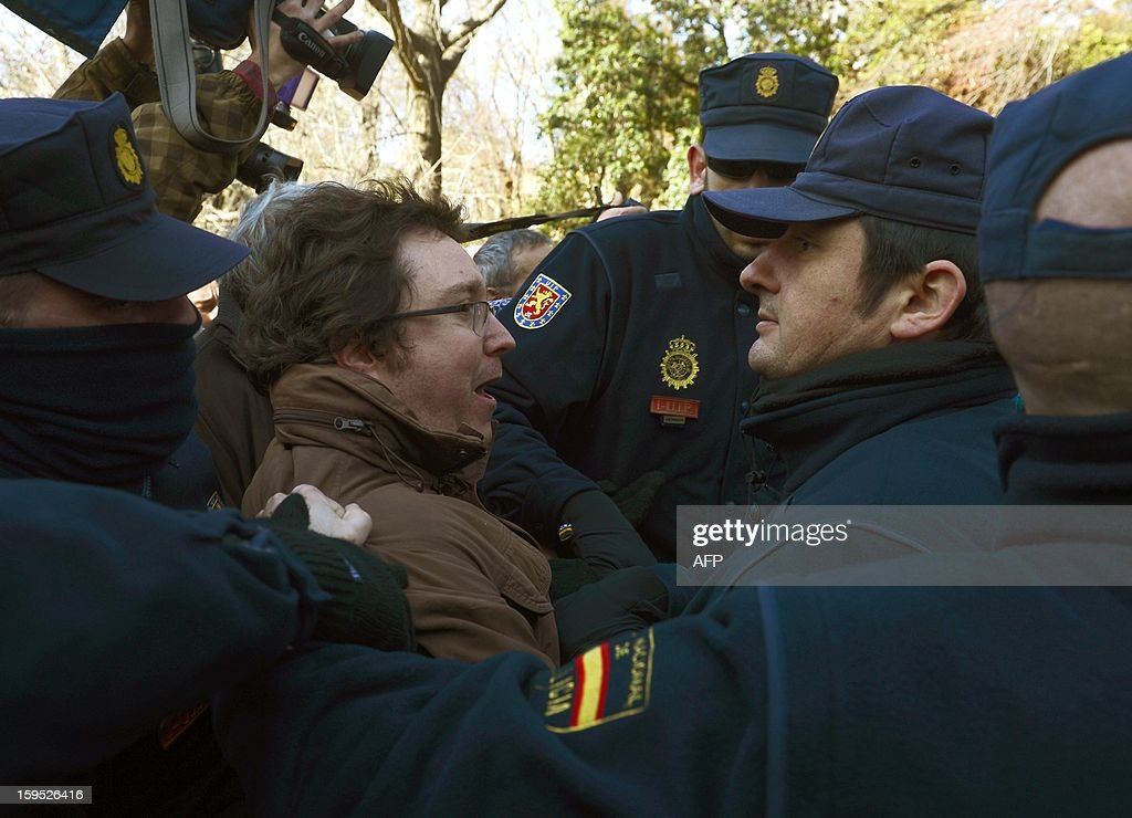 People facing foreclosure (C) protest in front of policemen securing a building where the Spain Investors Day (SID) forum is being held on January 15, 2013 in Madrid. Three people facing evictions had already committed suicide in Spain since october 2012. AFP PHOTO / PIERRE-PHILIPPE MARCOU