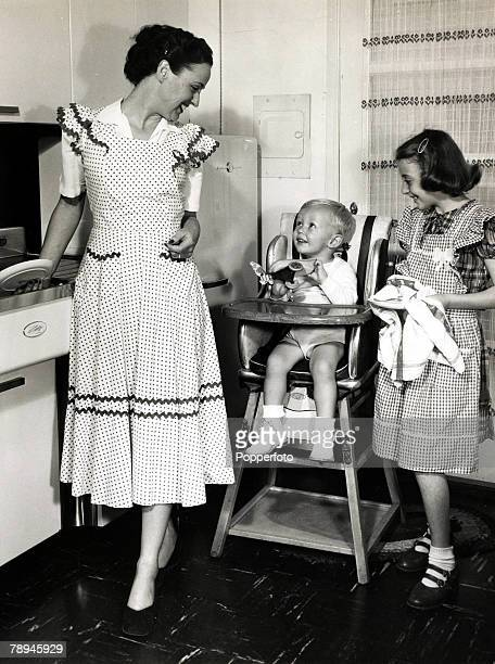 circa 1950's USA A mother with her older daughter helping dry the dishes and her toddler son sitting in a high chair