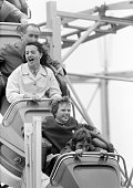 people family on the kermess Munich Beer Festival 1966 fun with a roller coaster ride man aged 35 to 40 years woman aged 30 to 35 years girl aged 11...