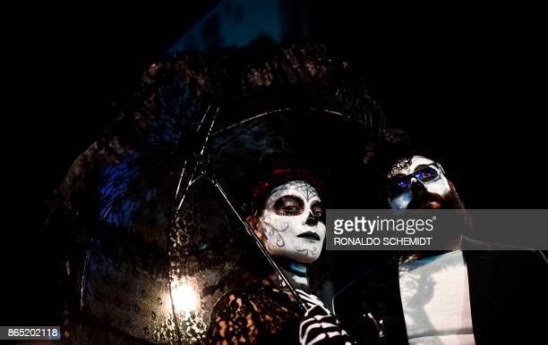 TOPSHOT People fancy dressed as 'Catrina' take part in the 'Catrinas Parade' along Reforma Avenue in Mexico City on October 22 2017 Mexicans get...