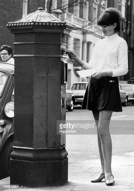 1968 Young woman dressed in a miniskirt posts a letter in Chelsea London