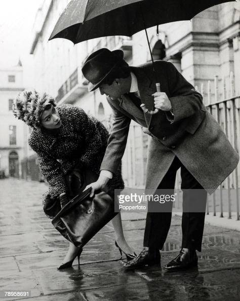 circa 1960 A man carrying an umbrella in the rain helps a woman retrieve her handbag from the wet pavement