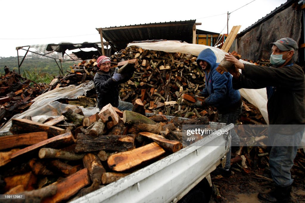 People fill a pick-up truck with lumber to sell for heating in the southern Lebanese city of Sidon, on January 8, 2013. Stormy weather, including high winds and heavy rainfall, lashed the eastern Mediterranean coast, downing power lines and trees and causing several injuries in a number of countries. AFP PHOTO / MAHMOUD ZAYYAT