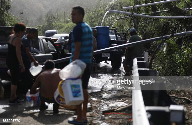 People fill containers with water funneled with pipes from a mountain stream nearly one month after Hurricane Maria struck on October 19 2017 in...