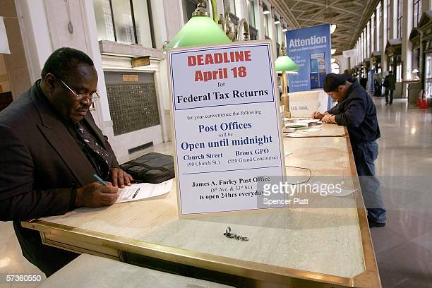 People fill out forms next to a sign declaring tax deadline day inside the Farley Post office April 18 2006 in New York City Monday was tax deadline...