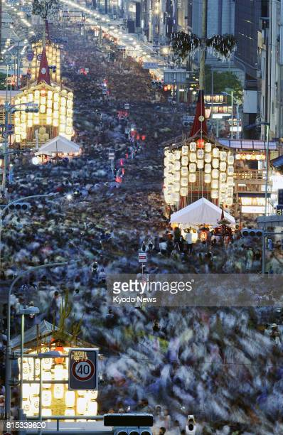 People fill the streets where floats with illuminated lanterns are on display during the Yoiyama Festival in Kyoto western Japan on July 16 2017...