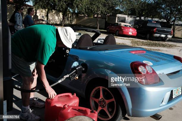 People fill up jerry cans at one of the few gas stations opened two days after Hurricane Irma swept through the area on September 12 2017 in Cape...