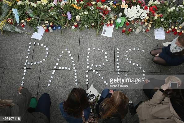 People finish arranging candles into the word 'Paris' next to flowers and messages left at the gate of the French Embassy following the recent terror...