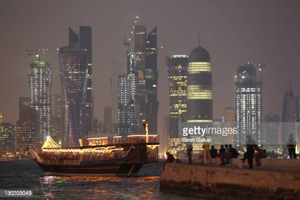 People fish along the waterfront along the Persian Gulf across from new illuminated financial district skyscrapers as a traditional Arab ship passes...