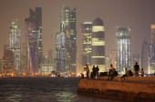 People fish along the waterfront along the Persian Gulf across from new illuminated financial district skyscrapers at dusk on October 24 2011 in Doha...