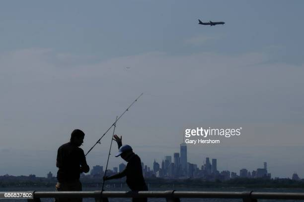 People fish in Jamaica Bay in Rockaway Park as an airplane approaches JFK Airport on May 21 2017 in New York City