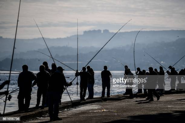 People fish on the Bosphorus river near tarabya district on a foggy day on October 15 2017 in Istanbul / AFP PHOTO / OZAN KOSE