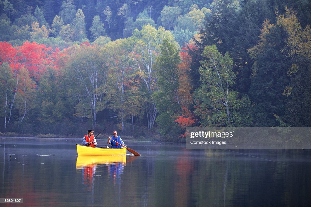People fishing from canoe