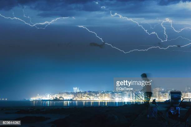 People fishing in Montevideo, under electric storm