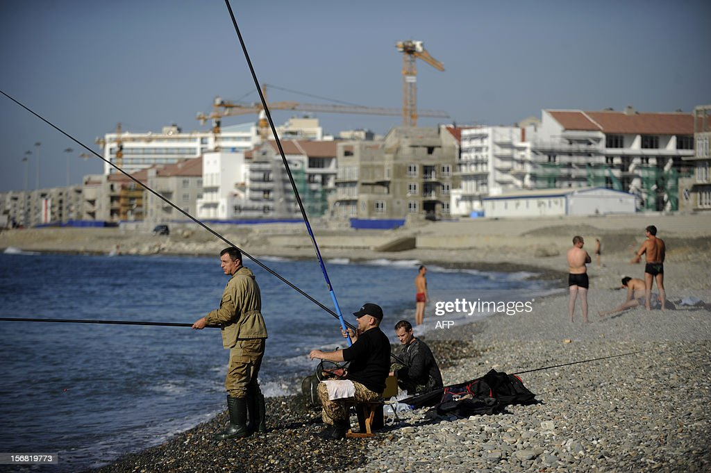 People fishing near the construction site of the Olympic Village (back) in the Imereti Valley in the Russian Black Sea resort of Sochi, on November 22, 2012. Sochi will host the 2014 Winter Olympics.